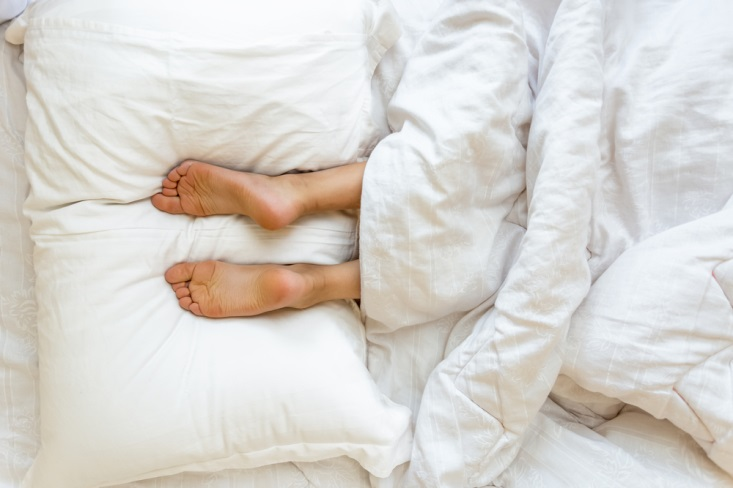 Image of feet on pillows - Microfiber Sheets Vs Cotton